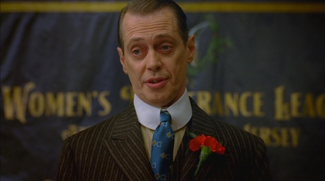 """Boardwalk Empire"" (episode 1.01): Nucky addresses the Women's Temperance League in a yellow striped shirt and blue square-patterned silk tie."