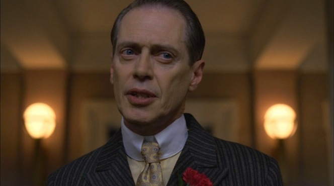 """A Return to Normalcy"" (episode 1.12): Nucky comes out strong against the D'Alessio brothers during a presser in which he wears a yellow shirt and yellow patterned silk tie."