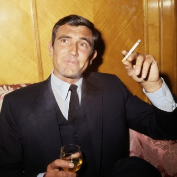 Lazenby sits with a drink and a smoke, easing into his role as 007 during the October 1968 presser.
