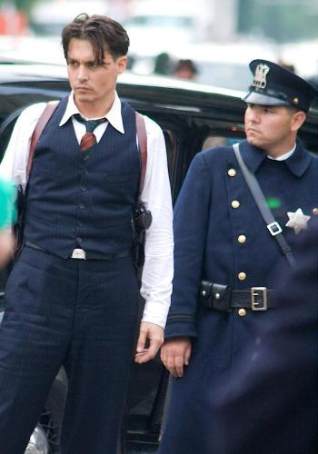 "Johnny Depp stands on set next to an extra decked out like a 1930s Chicago policeman. ""Why the mahoska?"" this officer should be asking."