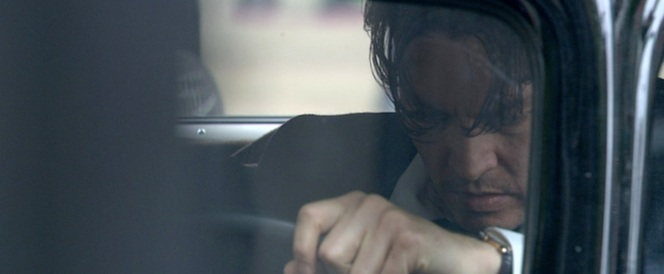 An intense-looking Dillinger weighs his options behind the wheel of his Buick.