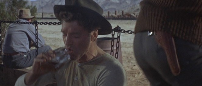 Bill Dolworth (Burt Lancaster) takes a drink as Rico's holstered revolver juts out from the back of his sweater.
