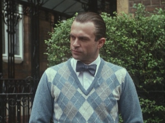 British spy meets Wall Street prepster as Sidney Reilly dons an argyle sweater, Winchester shirt, and bow tie.