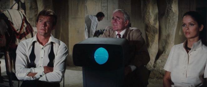 Bond watches Q's presentation with interest.