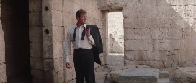 In the last 24 hours, Bond's been knocked around, drugged, and robbed, all under the blaring Egyptian sun. Yet, Roger Moore still exudes insouciant elegance and sophistication with his untied bow tie and dinner jacket removed and so rakishly flung over his left shoulder.