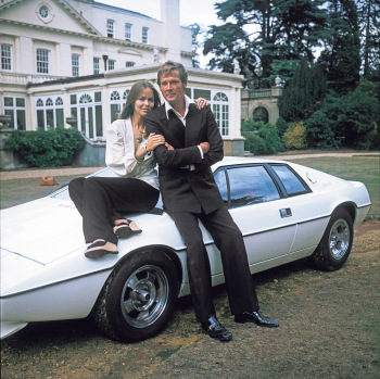 Promotional photo of Barbara Bach and Roger Moore (in double-breasted tux and loafers) leaning against that Lotus Esprit.