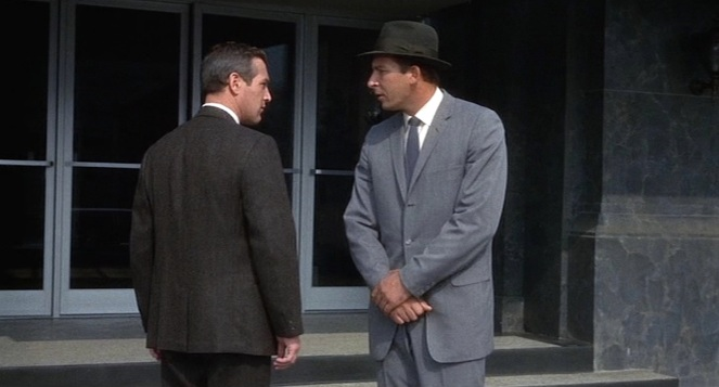 """""""A brown suit in the city? Surely you jest,"""" the man in gray seems to be saying to our protagonist."""