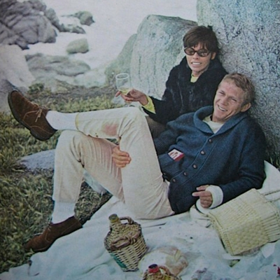 Steve McQueen kicks back in a navy shawl-collar cardigan in Carmel, 1964.