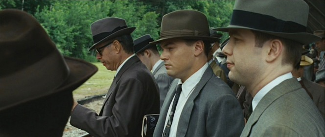 Frank takes his place among the other men in their business uniforms of two-piece suits, white shirts and ties, and fedoras.