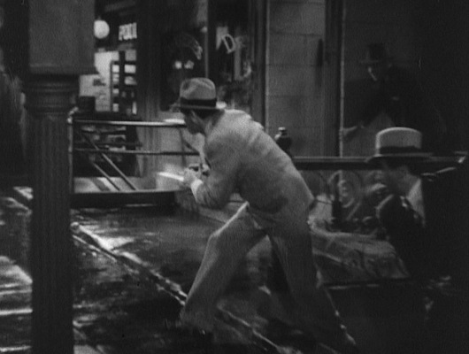 Tony leads his crew out to discover the corpse of a fellow gang member, his spats protecting those patent leather shoes against the dirty street.