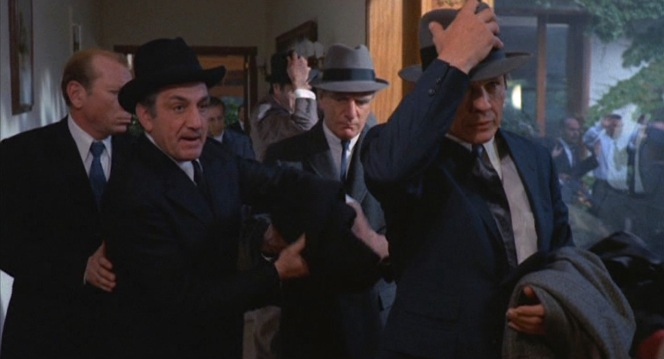 Valachi dons his hat when leading his boss Vito Genovese (Lino Ventura) and others out of the busted Apalachin meeting.