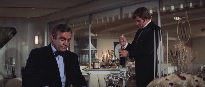 Mr. Wint (Bruce Glover) puts quite a show into opening a claret for Bond... unaware that it is a claret, of course, and sealing his own fate.
