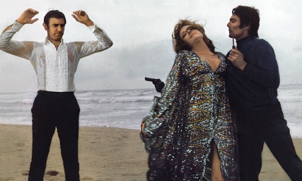 Production still of George Lazenby and Diana Rigg on the beach with a thug holding Bond at gunpoint.