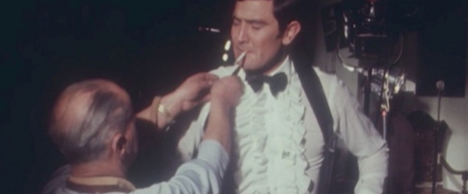 A behind-the-scenes shot from Becoming Bond of Lazenby being fitted into his shoulder holster on set.