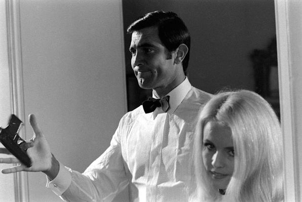 Lazenby during the audition process, twirling Bond's trademark PPK. French actress (and author) Marie-France Boyer turns away from the gunplay.