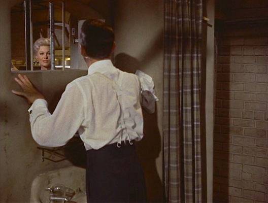 Joey catches Linda's eye through the barred window of his dressing room.