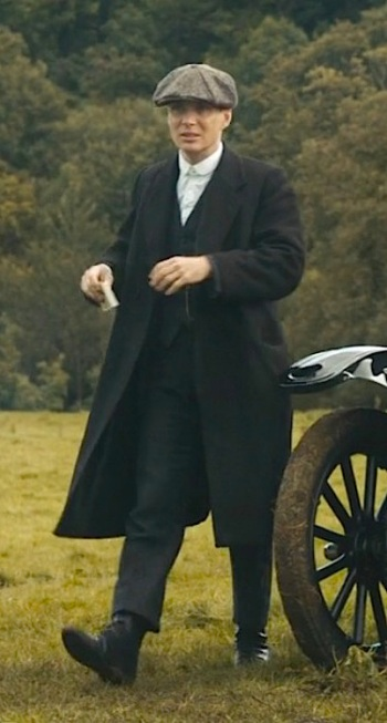 Cillian Murphy as Tommy Shelby on Peaky Blinders (Episode 2), stepping out of his Ford Model T in charcoal tweed suit and overcoat.