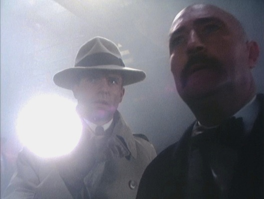 A scene from earlier in the episode as Reilly accompanies the sinister Soviet agent Monkewitz (Forbes Collins).