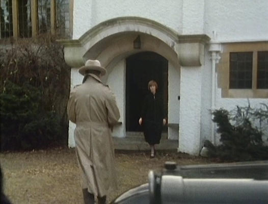 Reilly strolls into his home, where Eugenie is waiting at the door. Note the trench coat, fastened midway down the vent below the belt.