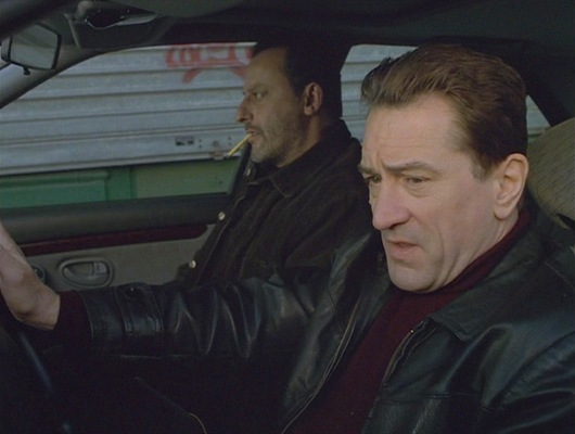 Sam, looking sleek and stylish in a maroon turtleneck jumper and black leather jacket with Vincent at his side.