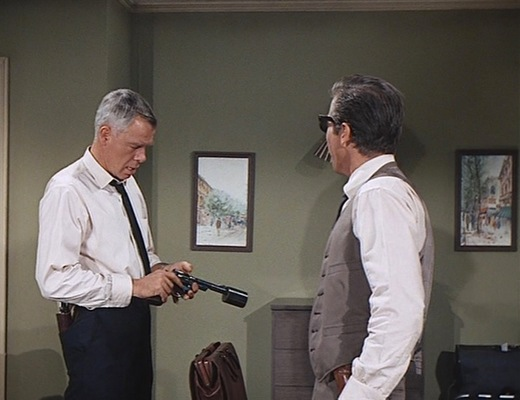 "Charlie Strom checks his ""suppressed"" Smith & Wesson Model 27 before leaving to confront Jack Browning. Note the Single Action Army holstered in his back trouser pocket."