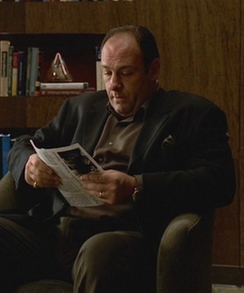 "James Gandolfini as Tony Soprano in The Sopranos episode ""Employee of the Month"" (Episode 3.04), following his usual template for wearing a black odd jacket with earth-toned trousers, silk pocket square, and dressed-down shirt."