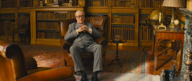 Arthur wears black cotton dress socks with his shoes rather than matching his hosiery to the lighter gray of his suit trousers.