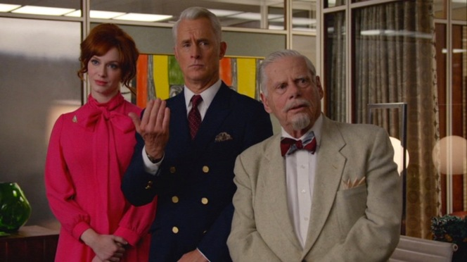 "Joan (Christina Hendricks), Roger (John Slattery), and Bert Cooper (Robert Morse) oversee SC&P's latest announcement in ""The Monolith"" (Episode 7.04)."