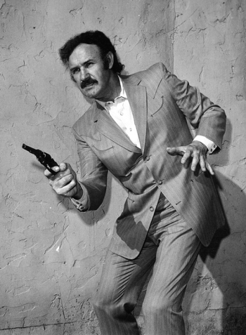 Promotional photo of Gene Hackman in Prime Cut (1972), sans tie and armed with a revolver rather than the 1911-style pistol he uses on screen.