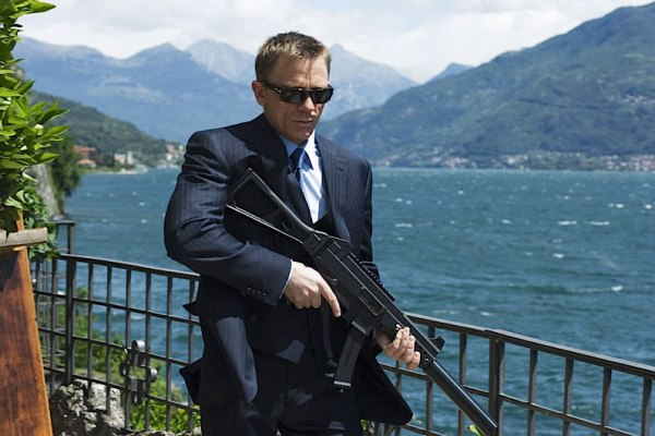Behind-the-scenes shot of Daniel Craig in Persol sunglasses and Brioni suit, brandishing 007's H&K MP-9 submachine gun. (Photo by Greg Williams)