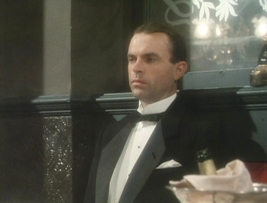 "Reilly sports a black wool notch-lapel dinner jacket for an evidently serious dinner with his friend and lawyer, Sasha Gramaticoff. The white pocket square only appears in ""Dreadnoughts and Doublecrosses"" (Episode 6)."