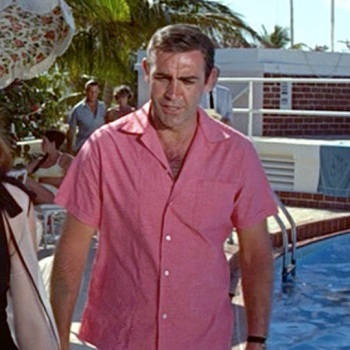 Pink linen camp shirt in Thunderball (1965), worn with light blue linen short-inseam swimming trunks and Rolex Submariner on a striped NATO strap.