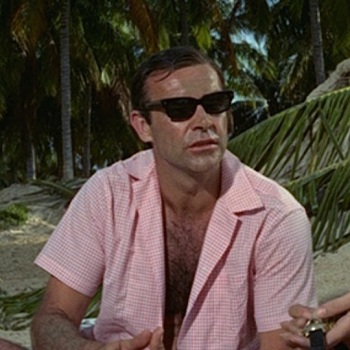 Pink-and-white gingham camp shirt in Thunderball (1965), worn with pink linen short-inseam swimming trunks, black sunglasses, and Rolex Submariner on a striped NATO strap.