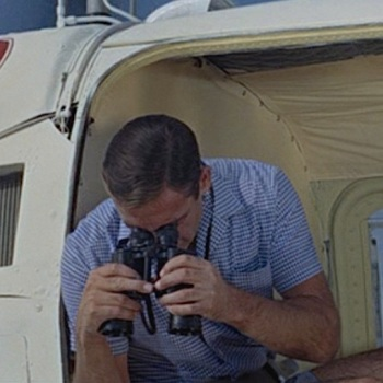 Blue-and-white gingham camp shirt in Thunderball (1965), worn with light blue linen short-inseam swimming trunks.