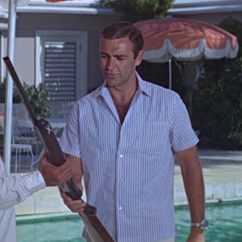 Slate blue-striped camp shirt in Thunderball (1965), worn with cream linen trousers, brown leather sandals, and steel Breitling Top Time dive watch. 007 holds Largo's Remington 1100 semi-automatic shotgun, though there's no good reason you'd need one of these for a beach getaway... depending on what kind of getaway it is, of course.