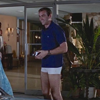 Navy cotton Fred Perry polo shirt in Thunderball (1965), worn with white short-inseam swim trunks, Rolex Submariner dive watch on undersized NATO strap, and light blue canvas espadrilles.