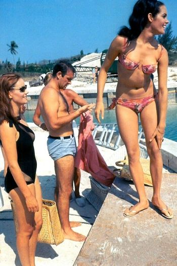 Sean Connery in his light blue linen Jantzen swim trunks, flanked by co-stars Claudine Auger and Martine Beswick, on location in the Bahamas for Thunderball (1965).
