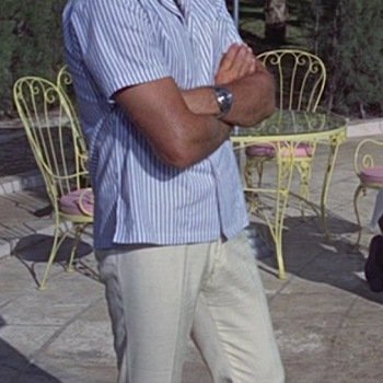 Cream linen trousers in Thunderball (1965), worn with a white-and-slate blue striped camp shirt, brown leather sandals, and Breitling Top Time dive watch.