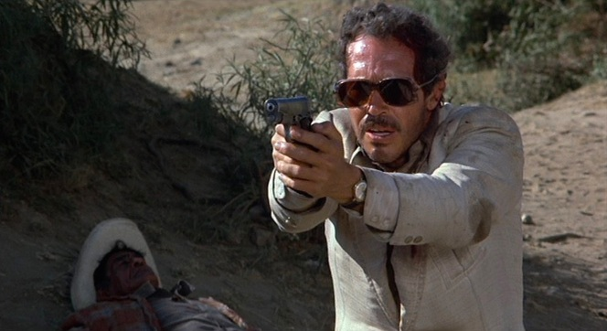 Bennie takes aim with his Colt Commander. Note the muzzle bore, indicating that his pistol is likely chambered in 9x19mm Parabellum rather than the larger .45 ACP. At the time of the film's production, .45 ACP blanks were notably unreliable with semi-automatic pistols and thus many movies and TV shows opted to use 9mm copies of the 1911 like the Spanish Star Model B or the Colt Commander, as featured here.)