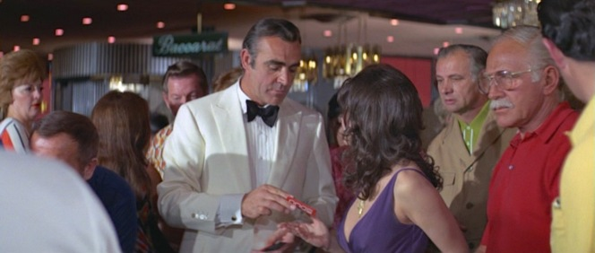 Plenty receives a well-earned $5,000 after the grueling task of merely standing next to James Bond for a few seconds.