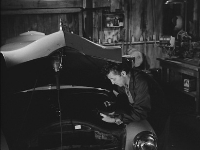"""Luke services his """"1950 Ford"""", though the hood's shadow cloaks the engine."""