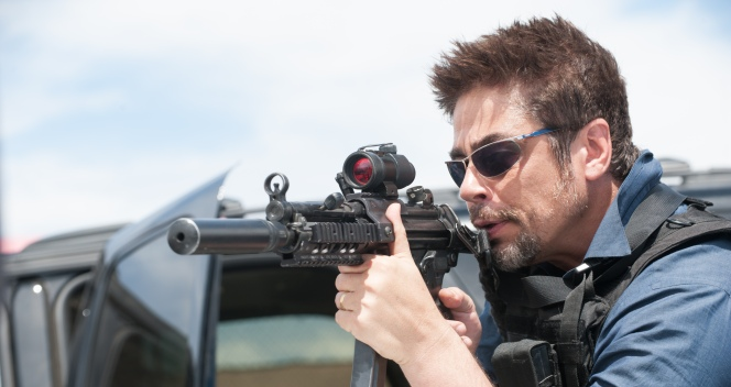 Production photo of Benicio del Toro taking aim with a suppressed Heckler & Koch MP5A3 in Sicario.