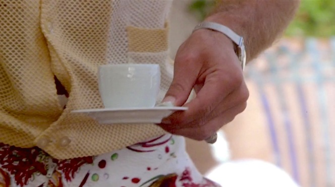 While the shot may be intended to focus on Dickie's coffee cup, it also gives the audience a closer look at the details of his shirt and shorts.