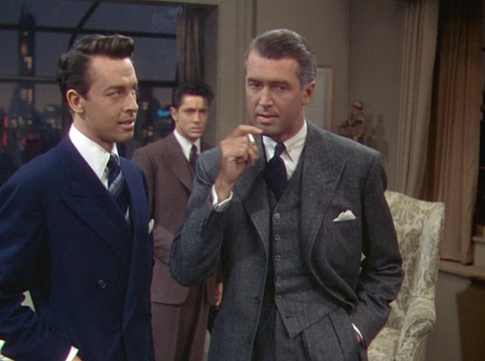 """Rupert's gray tweed suit bridges the gap between the cool, calculating Brandon in navy serge and the anxious, earthier Phillip in his brown striped suit. While gray can have businesslike connotations, the tweed suiting brings Rupert's ensemble """"down to earth"""" and subconsciously presents his morality more in line with the less murderous Phillip."""