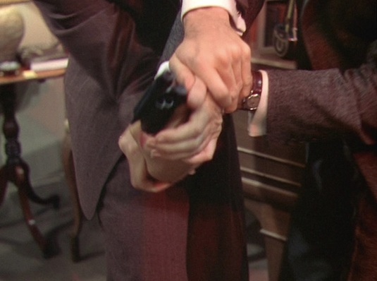 Rupert's watch flashes from his wrist as he and Phillip struggle for control of Brandon's discarded .38.