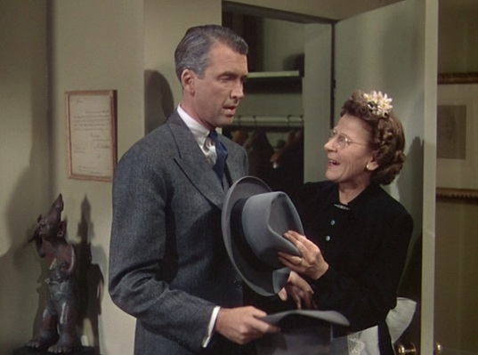 Brandon and Phillip's kind housekeeper, Mrs. Wilson (Edith Evanson), helps Rupert with his hat.