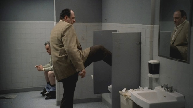 Tony's move of using his foot to flush the urinal is relatable, but Johnny Sack sitting on the toilet in a public bathroom without a door on the stall? Fuhgeddaboudit.