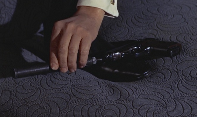 Grant flashes his cuff links as he balances Bond's PPK across his own shoe to attach the suppressor.