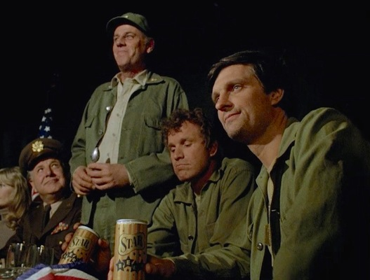 """Trapper John and Hawkeye celebrate the possibility of war's end with beer in """"Cease-Fire"""" (Episode 1.23)."""