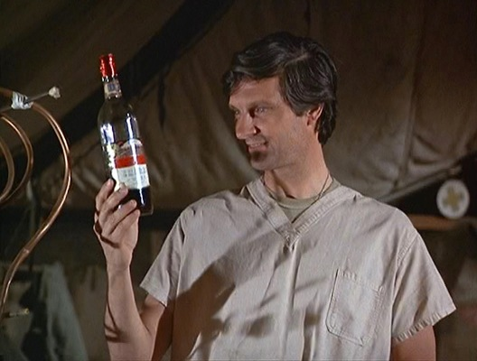 """Hawkeye stares at the """"red wine"""" he created in an empty vermouth bottle using gin and food coloring for his date with the wounded nurse, Lieutenant Erika Johnson (Joan Van Ark) in """"Radar's Report"""" (Episode 2.03)."""